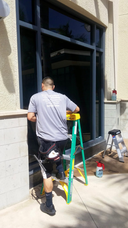 Technician installs privacy window film at Cavo Lounge in Naples, FL.