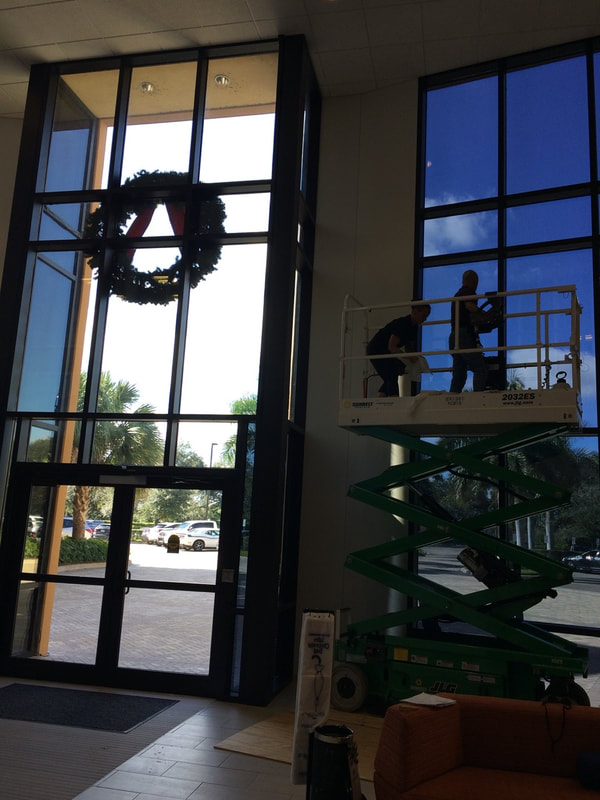 Installers adhering window films at Gartner Inc. Fort Myers