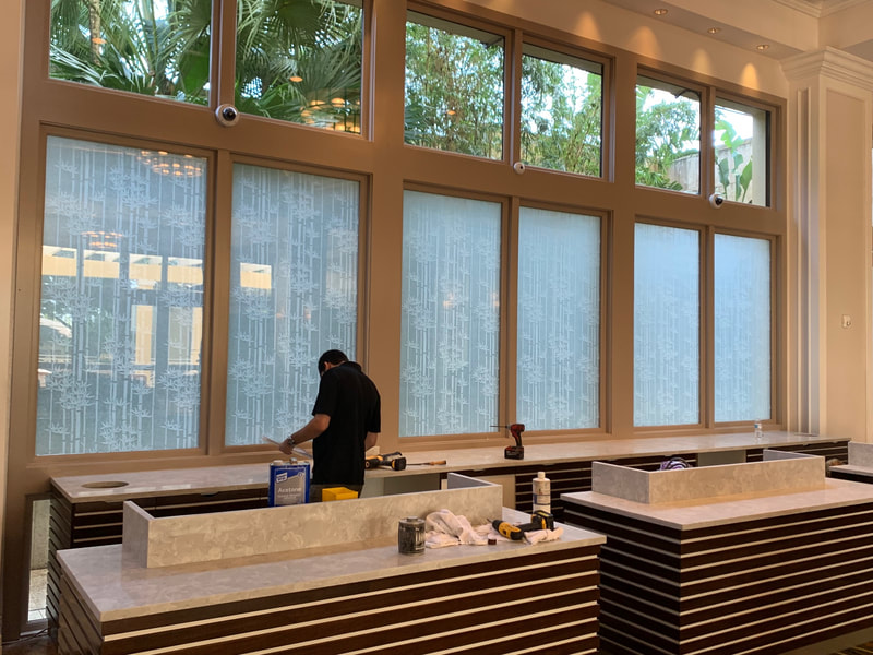 Technician installing privacy window films behind reservation desk at Hyatt Coconut Point.