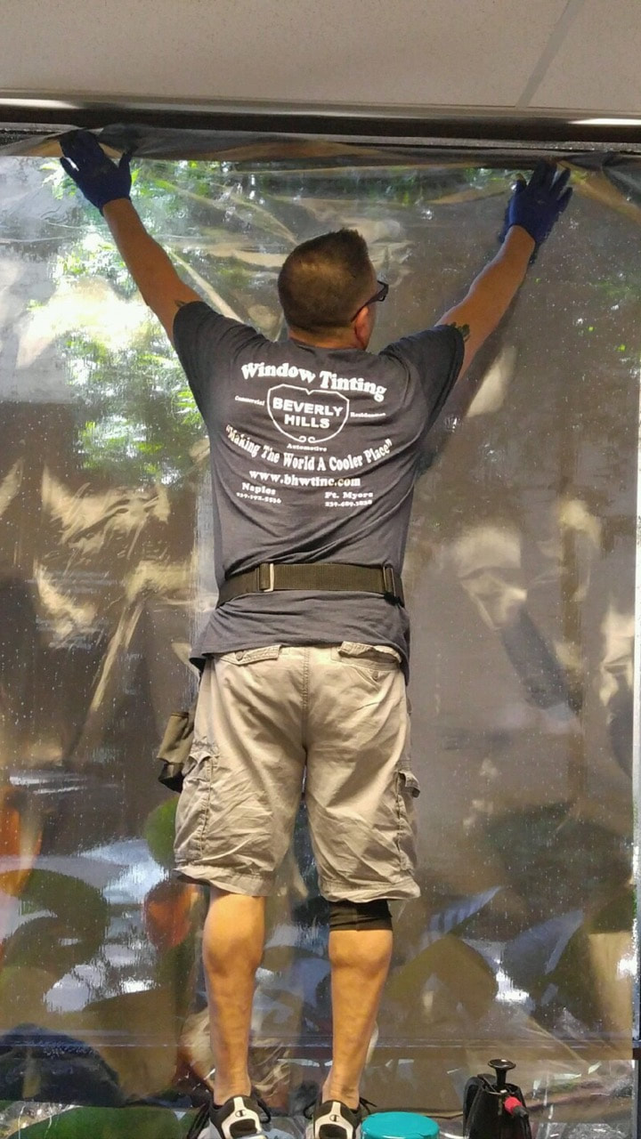 Paul Russo installing window film at Naples City Hall